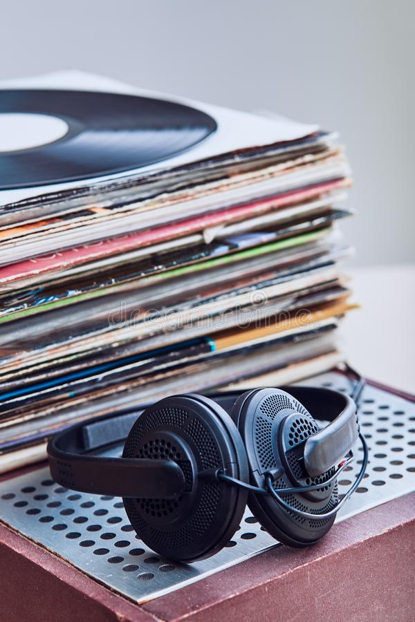 Stack of black vinyl records. Stack of many black vinyl records, headphones put on the top of vinyls. Copy space for text. Candid people, real moments, authentic royalty free stock images