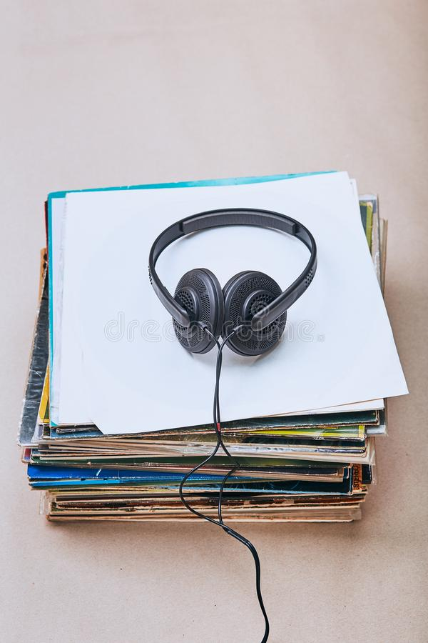 Stack of black vinyl records. Stack of many black vinyl records and headphones on the top of stack. Candid people, real moments, authentic situations stock image