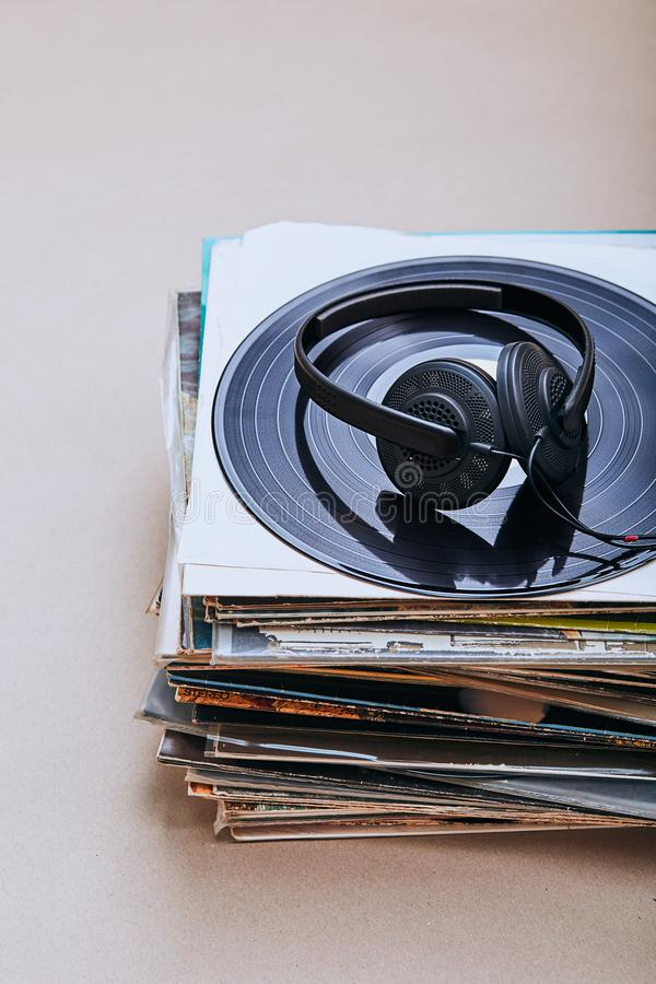 Stack of black vinyl records. Stack of many black vinyl records and headphones on the top of stack. Candid people, real moments, authentic situations stock photo
