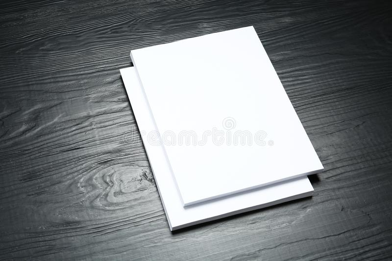 Stack of blank paper sheets for brochure on black wooden background. Mock up royalty free stock photography