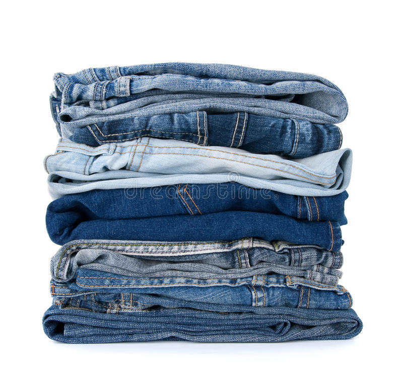 Stack of blue denim clothes. On white background, jeans and jacket stock image