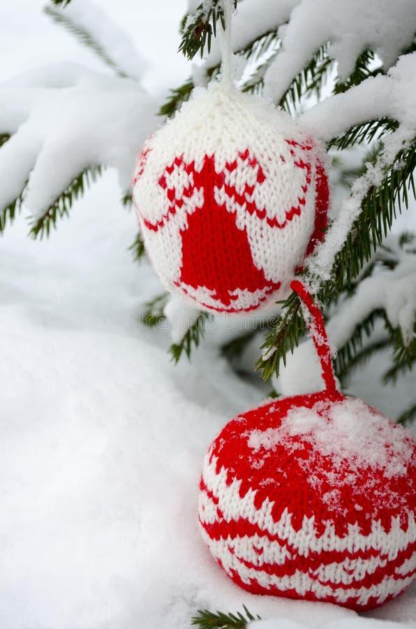 Stack bollar för garnering för nytt år som och julgranhänger på den prydliga filialen som täckas med snö arkivbilder