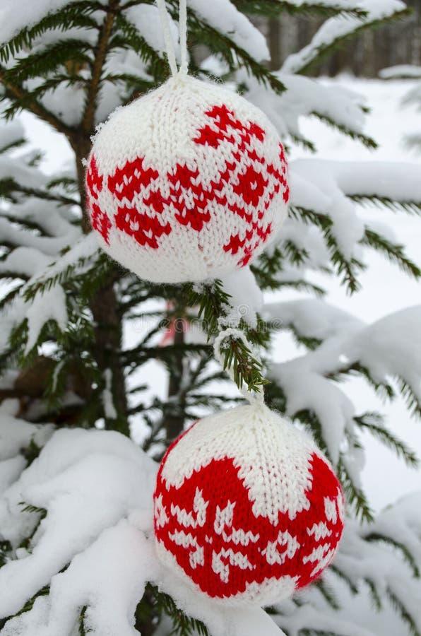 Stack bollar för garnering för nytt år som och julgranhänger på den prydliga filialen som täckas med snö fotografering för bildbyråer