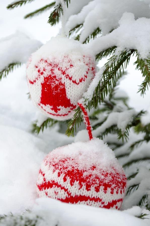 Stack bollar för garnering för nytt år som och julgranhänger på den prydliga filialen som täckas med snö royaltyfria foton