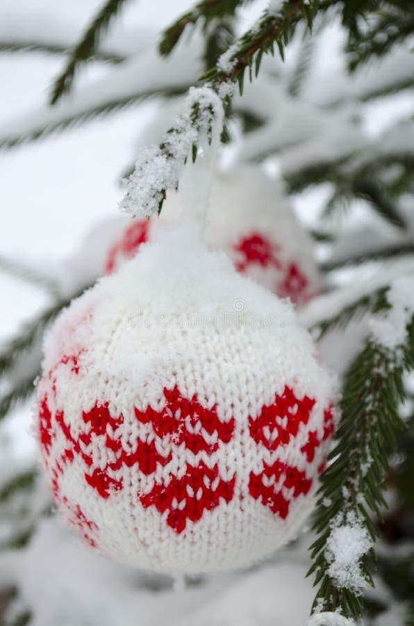 Stack bollar för garnering för nytt år som och julgranhänger på den prydliga filialen som täckas med snö royaltyfri foto