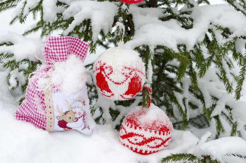 Stack bollar med prydnaden och påsen för nytt år under det prydliga trädet som täckas med snö fotografering för bildbyråer