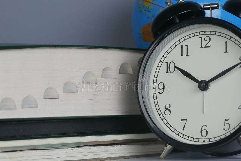 Stack of book with globe and clock. Education ,time and world concept royalty free stock image