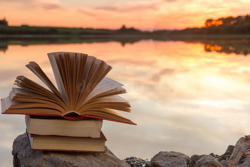 Stack of book and Open hardback book on blurred nature landscape backdrop against sunset sky with back light. Copy space, back to royalty free stock photography