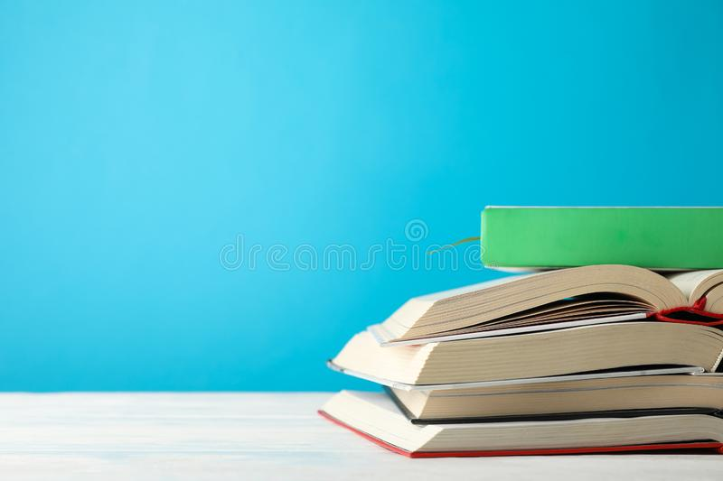 Stack of books against blue background. Space for text stock image