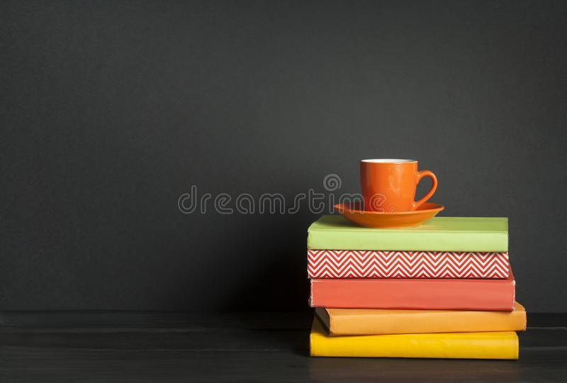 Stack of colorful books and cup of coffee on the wooden table. Education background. Back to school.Copy space for text. stock images