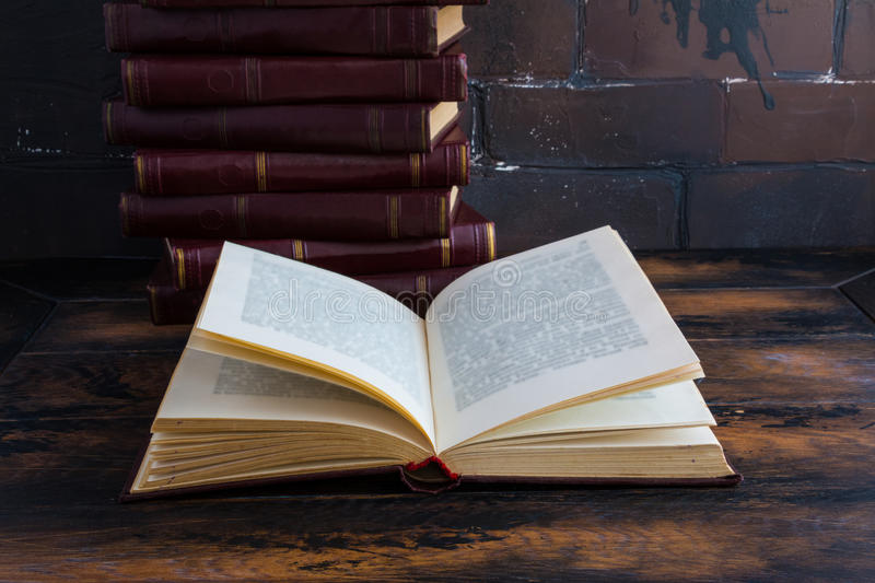 A stack of books with a dark red hard cover one another and open book on a wooden table against the background of brown brick wall royalty free stock photos