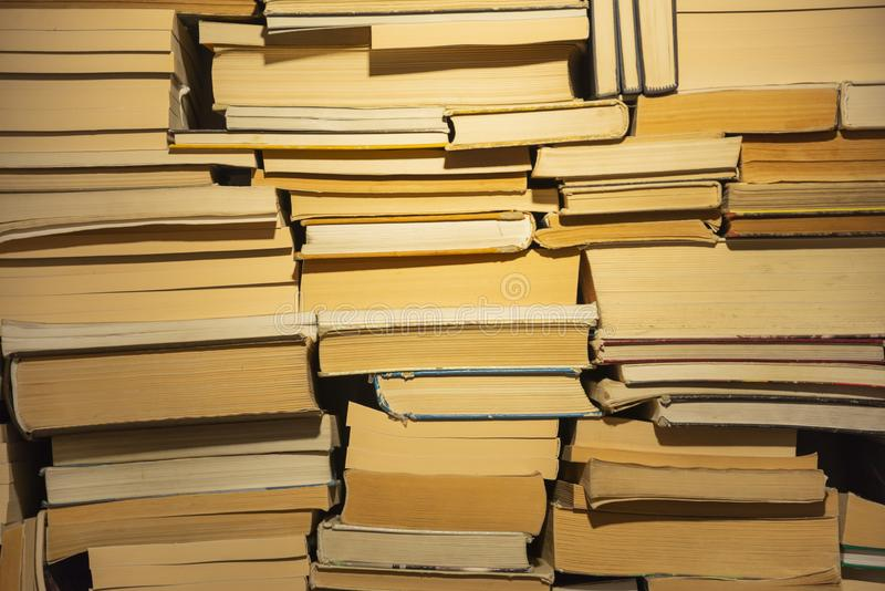 Stack of books of different size on the shelf. View from the butt on the old books. Close-up view royalty free stock image