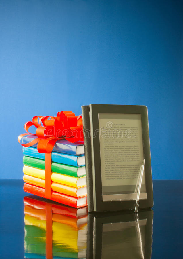 Stack of books with electronic book reader. Against blue background stock image