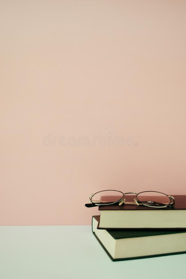 Stack of books in front of pale pink pastel background. Minimal lifestyle composition with copy space. Stack of books in front of pale pink pastel background royalty free stock image
