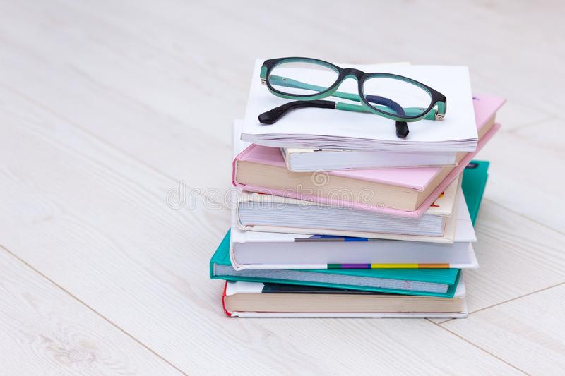 Stack of books with glasses on top. Concept cause of farsightedness, myopia. Stack of books with glasses on top on wooden background. Concept cause of royalty free stock images