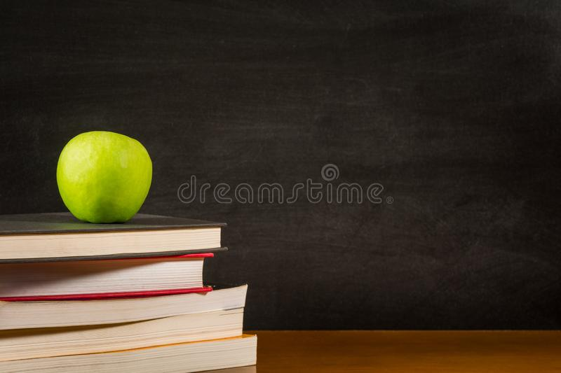 Stack of books and a green apple on a desk front of a blank blackboard stock photos