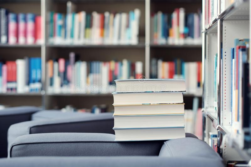 Stack of books in a library. Stack of books on a couch in a library, shelf, read, white, education, study, school, learn, yellow, information, colledge, degree royalty free stock photo
