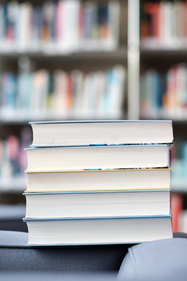 Stack of books in a library. Stack of books on a couch in a library, shelf, read, white, education, study, school, learn, yellow, information, colledge, degree stock photography