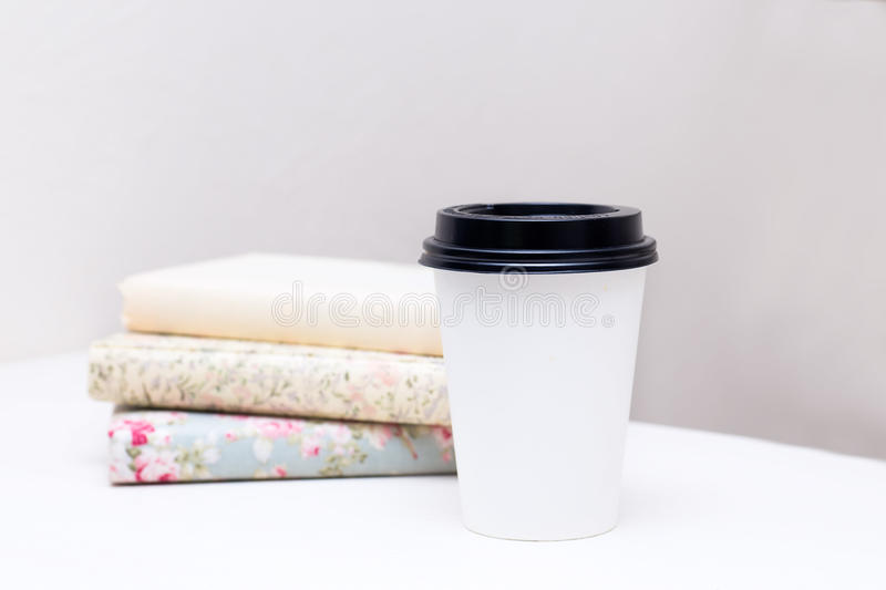 Stack of books and paper cup at the table stock image