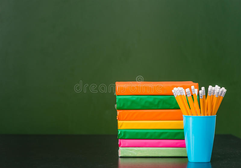 Stack of books and pencils near empty green chalkboard royalty free stock images