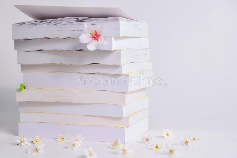 A stack of books on a table with flowers between the pages stock photos