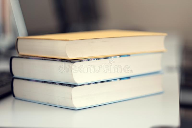 Stack of books on a table. In a library, shelf, read, white, education, study, school, learn, yellow, information, colledge, degree, student, schoolboy, blue royalty free stock photos