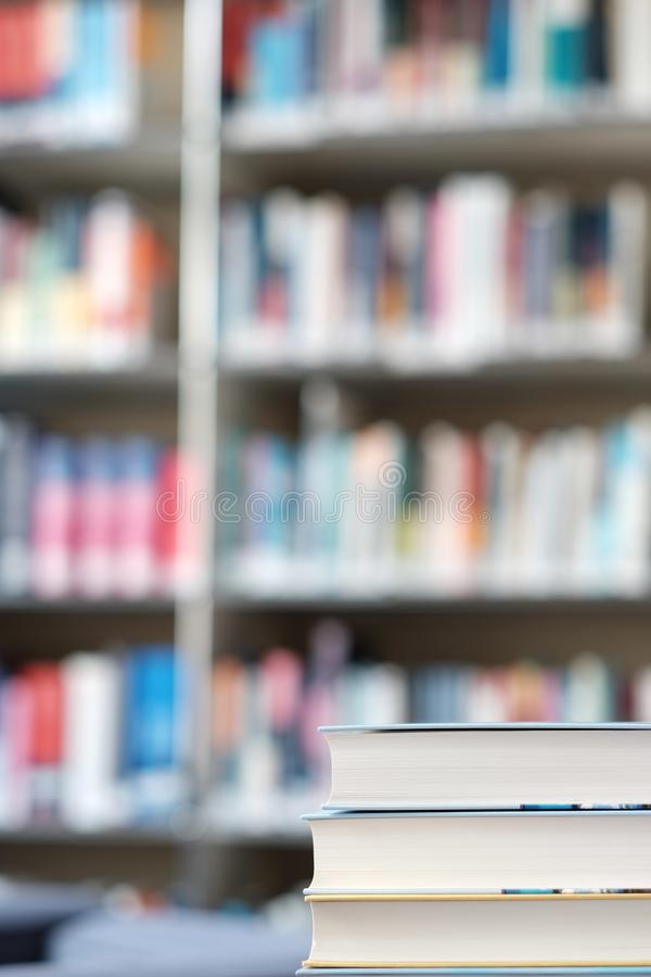 Stack of books in a library. Stack of books on a table in a library, shelf, read, white, education, study, school, learn, yellow, information, colledge, degree royalty free stock image