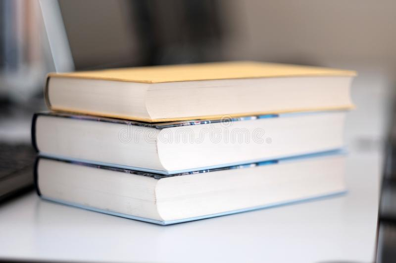 Stack of books on a table. In a library, shelf, read, white, education, study, school, learn, yellow, information, colledge, degree, student, schoolboy, blue stock photos
