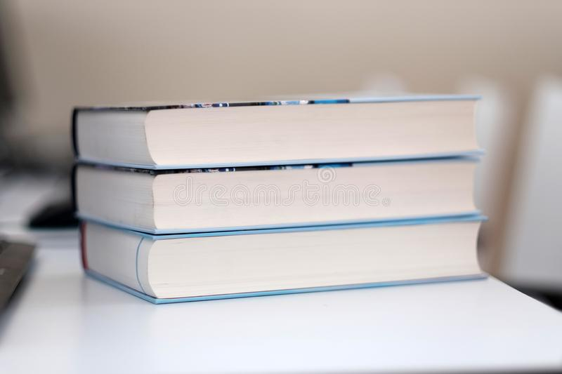 Stack of books on a table. Stack of books on a shelf in a table, library, read, white, education, study, school, learn, yellow, information, colledge, degree stock images