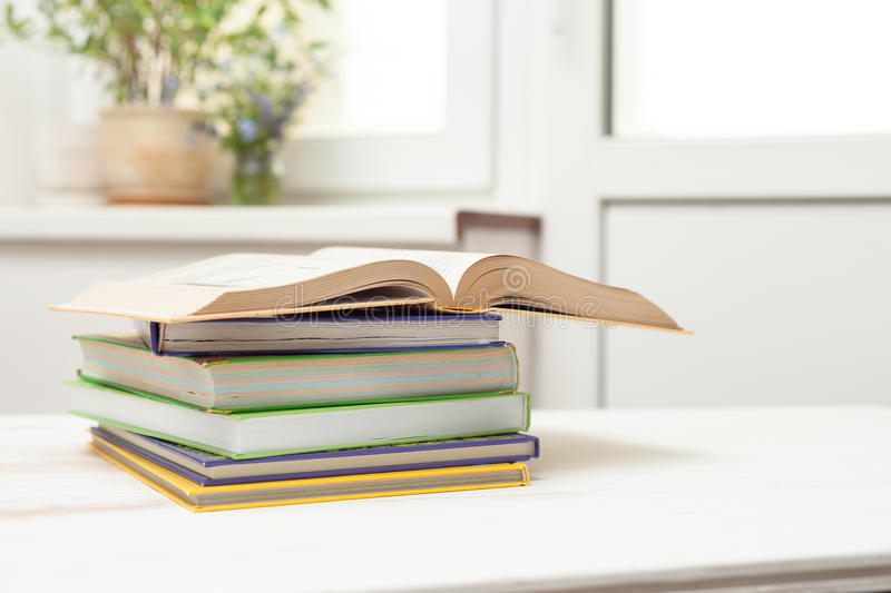 A stack of books on a white table. Art coloured stack of books and open book on white table on window background stock image