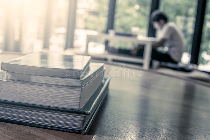 Stack of books on wooden table on blur people read a book. Background in vintage color filter royalty free stock image
