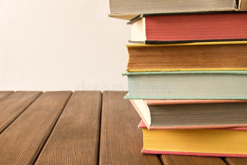 Stack of books on a wooden table. The concept of education and knowledge from books. Close up. With empty space for text. stock photography