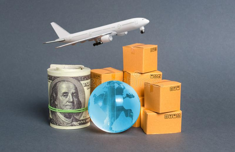 A stack of boxes, airplane a bundle of dollars and a blue planet earth globe. World trade and commodity exchange. commerce traffic. Trading balance. Import stock photography