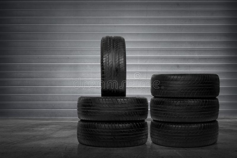 Stack of car tires. Over metal roller shutter background royalty free stock image