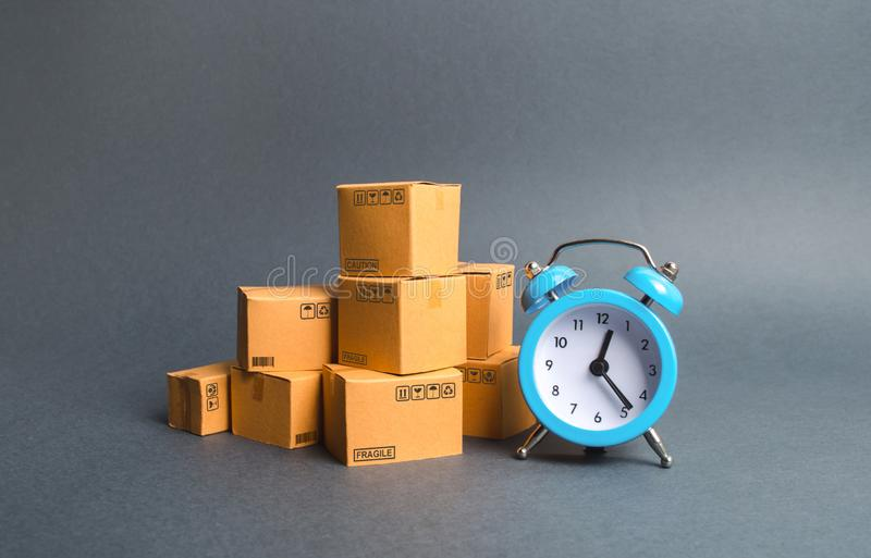 A stack of cardboard boxes and a blue alarm clock. Express delivery concept. Temporary storage, limited offer and discount. stock images