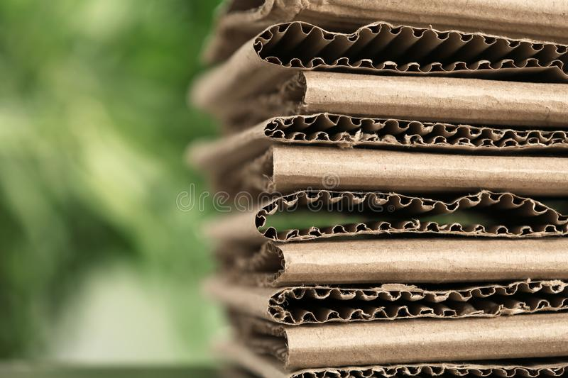 Stack of cardboard for recycling on blurred background, closeup. Space for text stock photo