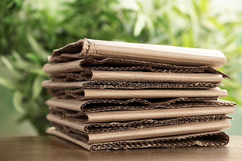Stack of cardboard for recycling on table. Against blurred background royalty free stock image