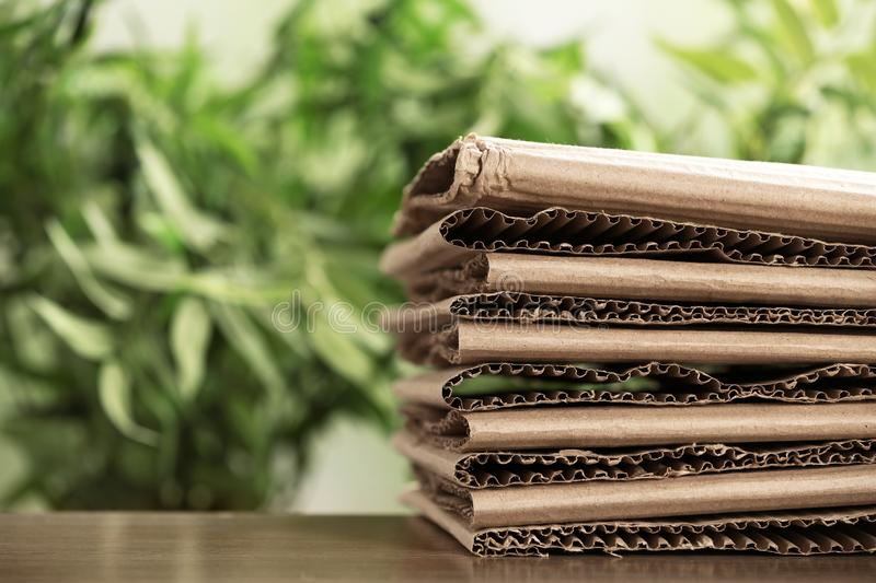 Stack of cardboard for recycling on table against blurred background. Space for text royalty free stock image