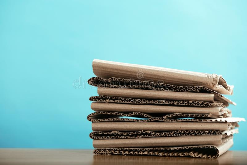 Stack of cardboard for recycling on table against color background. Space for text stock photo