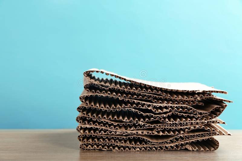 Stack of cardboard for recycling on table against color background. Space for text royalty free stock image