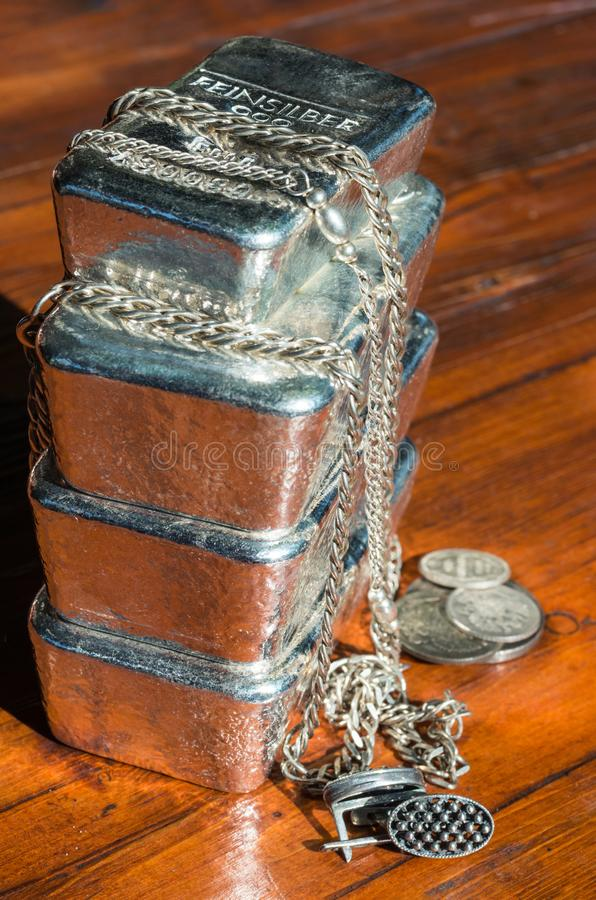 A stack of cast silver bars, coins and jewelry. On the background of mahogany. feinsilber = fine silver royalty free stock image
