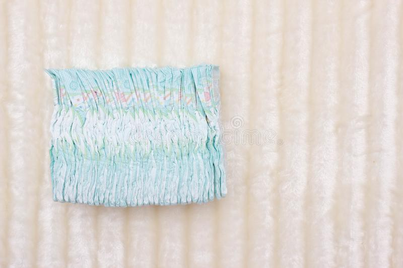 A stack of children`s hypoallergenic diapers on a white background, protection against leakage, dryness, copy space. Hygienics stock photo