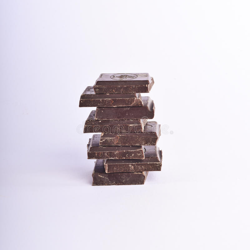 Stack of chocolate pieces on a white background. stock image