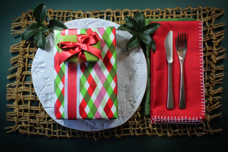 Stack of Christmas gifts on a white plate with holly and red napkins royalty free stock photos