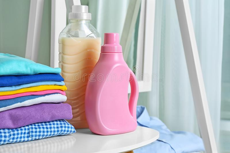 Stack of clean clothes and bottles with detergent. On table stock photo
