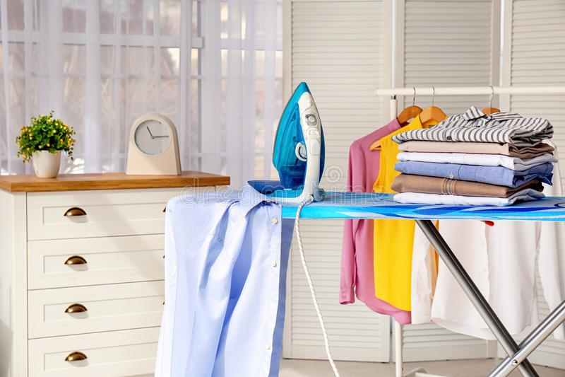Stack of clean clothes and iron on board. Indoors royalty free stock photography