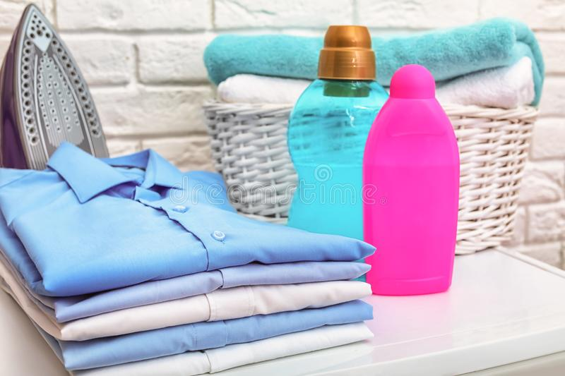 Stack of clean clothes, iron, detergents. And basket with towels on table royalty free stock photos