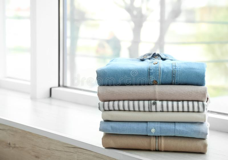 Stack of clean clothes on sill. Stack of clean clothes on window sill stock images