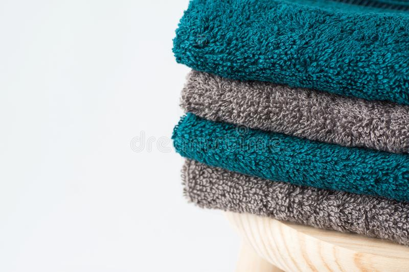 Stack of clean folded navy turquoise beige terry towels on wooden chair white wall background. Laundry spa wellness cleanliness. Concept. Scandinavian style royalty free stock image