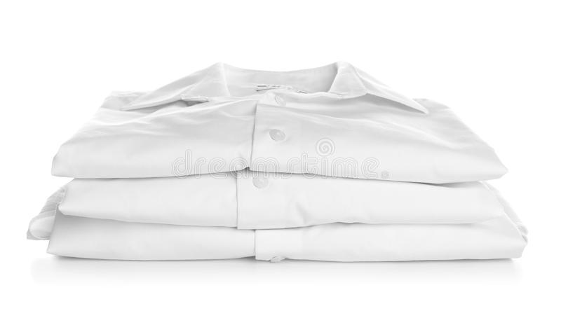 Stack of clean folded shirts on white background. Laundry day stock photography